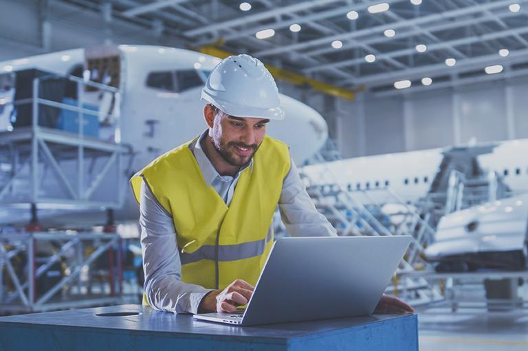 inżynier używający laptopa przy samolocie