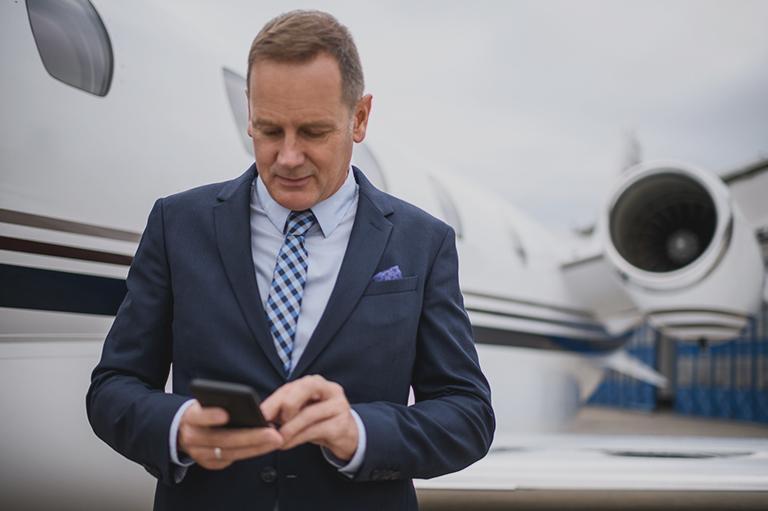 mężczyzna ztelefonem przy samolocie