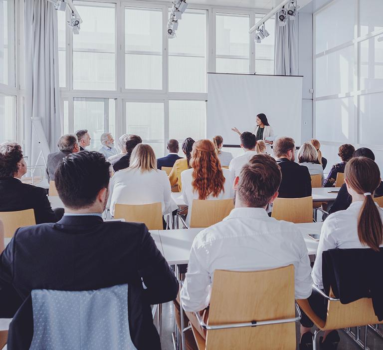 grupa osób słuchająca szkolenia kobiety